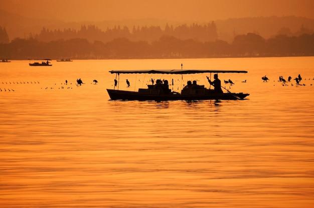 Pomarańczowy krajobraz rybaka w swojej łodzi