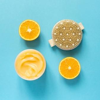 Pomarańczowy krem antycellulitowy i szczoteczka do masażu suchego na niebieskim tle, widok z góry.
