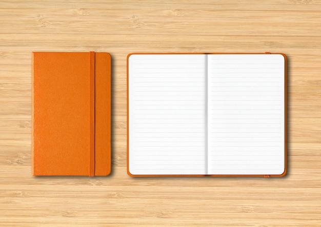 Pomarańczowy makieta zeszytów zamknięte i otwarte na białym tle na drewniane
