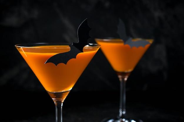 Pomarańczowy martini dyni halloween pić na imprezę na czarnym tle z miejsca na kopię