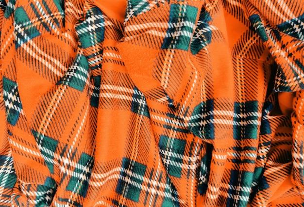 Pomarańczowy materiał w kratę zmięty tło