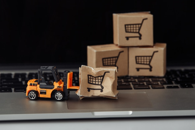 Pomarańczowy model wózka widłowego i zepsuty karton na klawiaturze. koncepcja wypadku usługi kurierskie i przesyłki