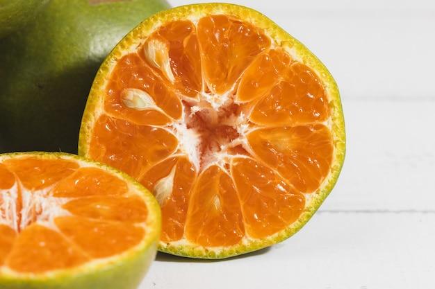 Pomarańczowy na białym drewnianym tle dla owoców i koncepcji jedzenia