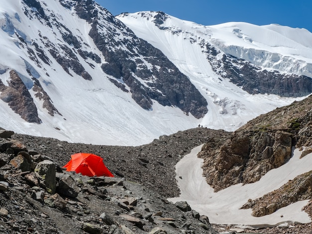 Pomarańczowy namiot na lodowcu. ekstremalny nocleg w górach. spokój i relaks na łonie natury.