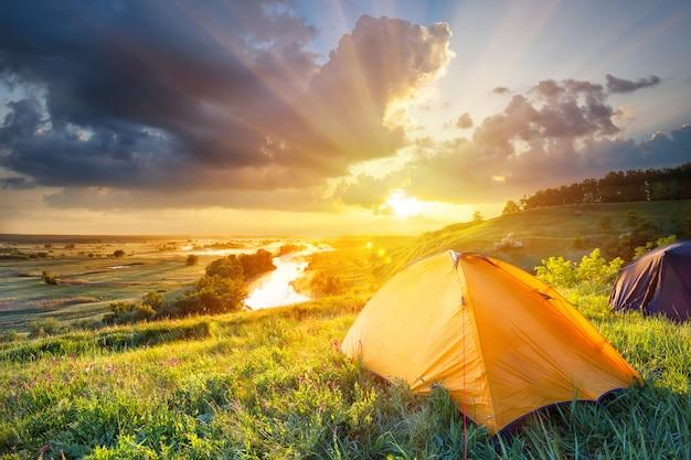 Pomarańczowy namiot na zboczu wzgórza w jasnym słońcu