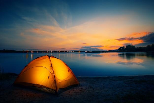 Pomarańczowy namiot nad jeziorem o zmierzchu
