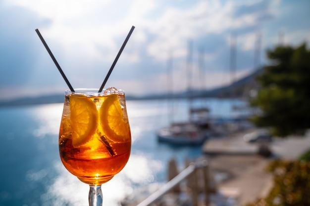 Pomarańczowy napój lub koktajl stojący przy stoliku w restauracji lub kawiarni na tle morza