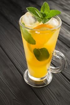 Pomarańczowy napój lub lemoniada z miętą i lodem w szklance na czarnym tle drewnianych. zbliżenie. lokalizacja w pionie.