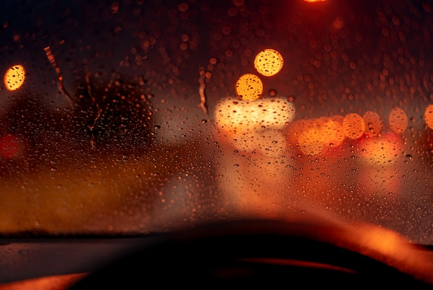 Pomarańczowy nocy światła bokeh od latarni ulicznej na korku dnia. deszczowy dzień. przezroczyste szklane okno z kroplą deszczu. romantyczna pogoda. życie w mieście.