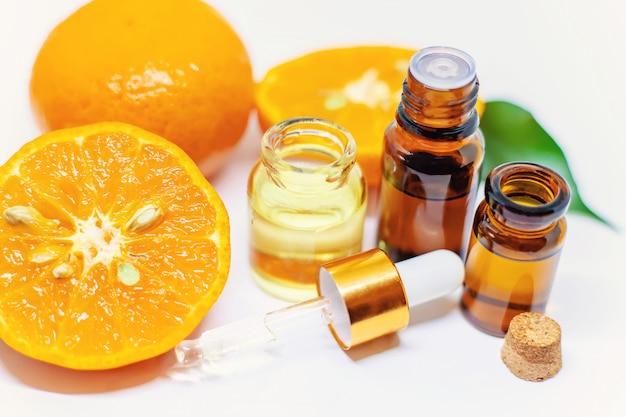 Pomarańczowy olejek eteryczny w butelce i pomarańczach