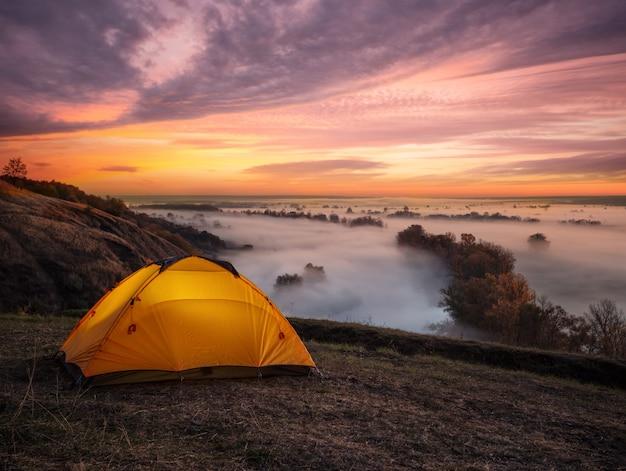 Pomarańczowy oświetlony z wnętrza namiotu nad rzeką o zachodzie słońca