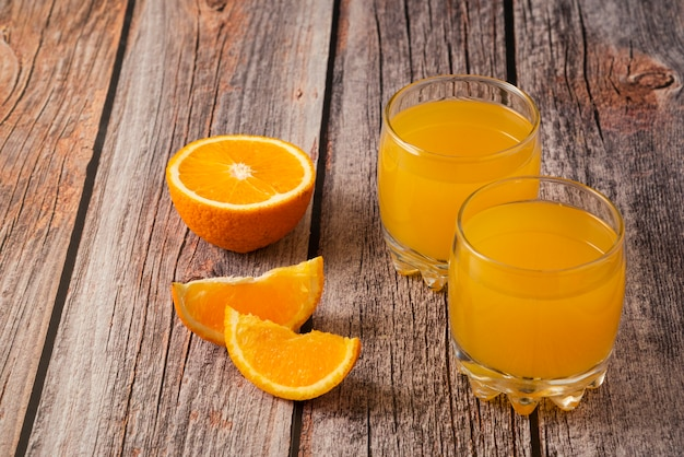 Pomarańczowy owoc ze szklanką soku na drewnianym stole