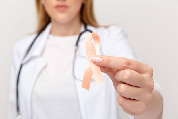 Pomarańczowy ribbone w ręce lekarza na białym tle.