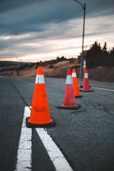 Pomarańczowy ruch drogowy rożek na szarej asfaltowej drodze podczas dnia