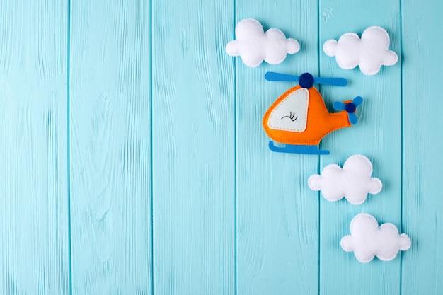 Pomarańczowy rzemiosło helikopter, chmury na błękitnym drewnianym tle z copyspace i. czuł ręcznie robione zabawki.