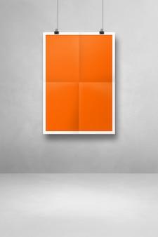 Pomarańczowy składany plakat wiszący na białej ścianie z klipsami. pusty szablon makiety