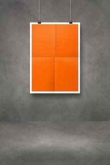 Pomarańczowy składany plakat wiszący na ciemnej betonowej ścianie z klipsami. pusty szablon makiety