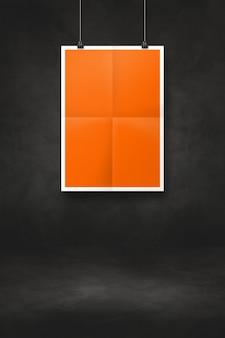 Pomarańczowy składany plakat wiszący na czarnej ścianie z klipsami. pusty szablon makiety