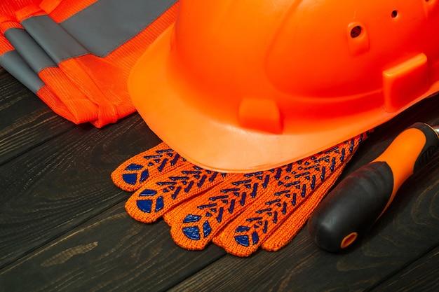Pomarańczowy sprzęt ochronny mistrza budowniczego ułożony w stos