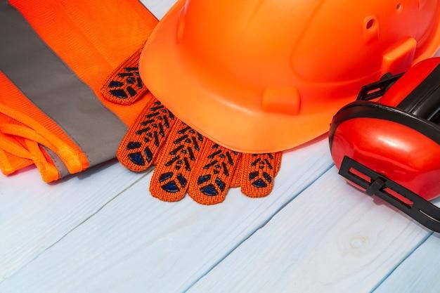 Pomarańczowy sprzęt ochronny mistrzów budowniczych ułożony na niebieskich tablicach