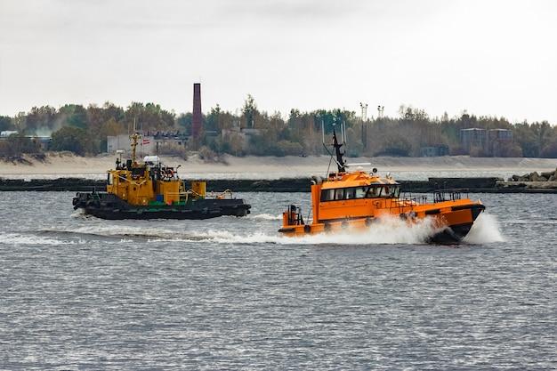 Pomarańczowy statek pilotowy poruszający się z prędkością obok holownika w rydze