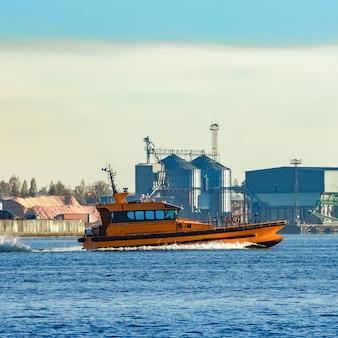 Pomarańczowy statek pilotowy przepływający obok fabryki na łotwie