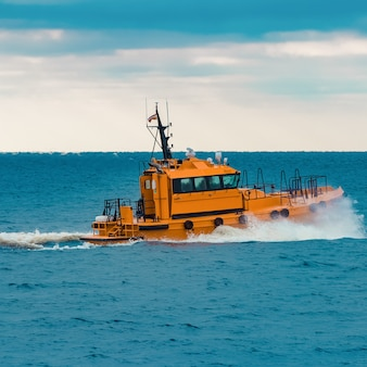 Pomarańczowy statek pilotowy szybko poruszający się po morzu bałtyckim. europa