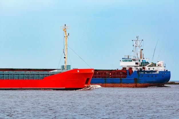 Pomarańczowy statek towarowy przepływający obok niebieskiego masowca