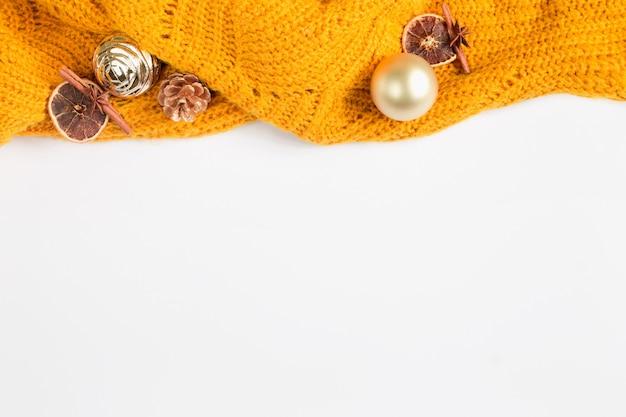 Pomarańczowy sweter z bożymi narodzeniami bawi się na białym tle