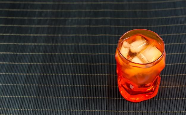 Pomarańczowy szklankę wody z lodem na czarnej powierzchni bambusa