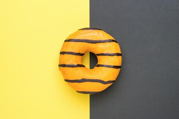 Pomarańczowy szkliwiony donut na granicy żółtego i czarnego koloru. popularna słodka przekąska.