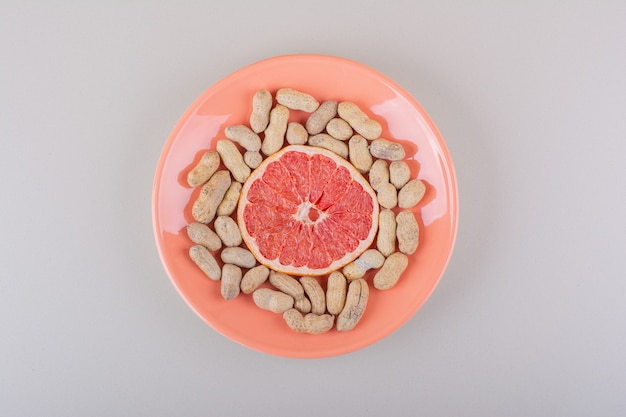 Pomarańczowy talerz plasterka grejpfruta i organicznych orzeszków ziemnych na białym tle. zdjęcie wysokiej jakości