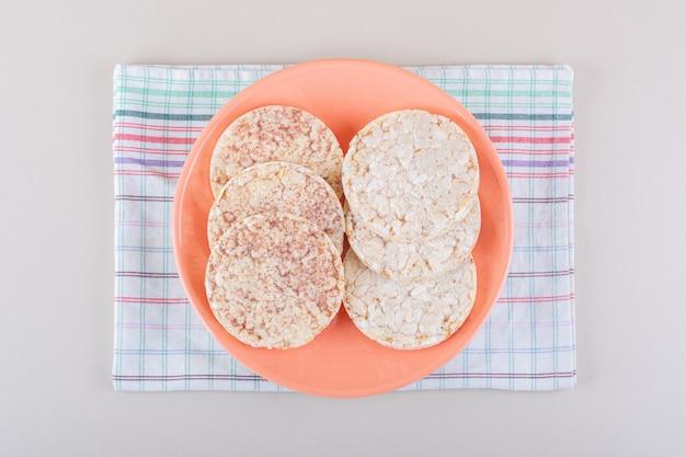 Pomarańczowy talerz pysznych ciastek ryżowych na białym stole. wysokiej jakości zdjęcie