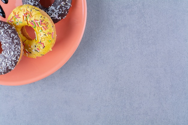 Pomarańczowy talerz pysznych czekoladowych pączków z posypką.