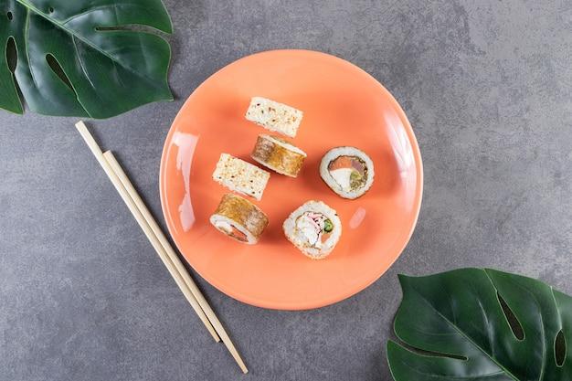 Pomarańczowy talerz rolek sushi z tuńczykiem na kamiennym tle.