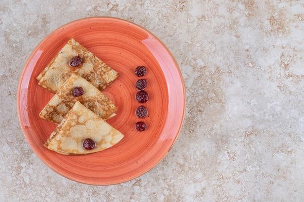 Pomarańczowy talerz z pysznymi cienkimi naleśnikami i jagodami