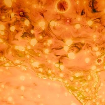 Pomarańczowy tło z złotymi światłami abstrakcjonistycznymi