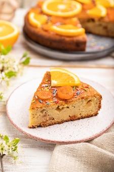 Pomarańczowy tort i filiżankę kawy na białym tle drewniane i lnianą tkaniną.