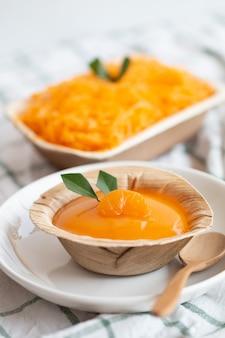 Pomarańczowy tort z polewą z pomarańczowego sosu w kubku nuturalnym, zapisz opakowanie ziemi