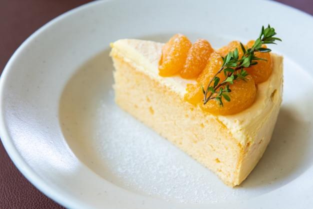 Pomarańczowy tort z pomarańczową owocową polewą na białym naczyniu