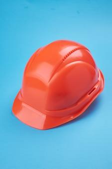Pomarańczowy twardy kask ochronny na niebiesko. orientacja pionowa. koncepcja budownictwa i robót usługowych