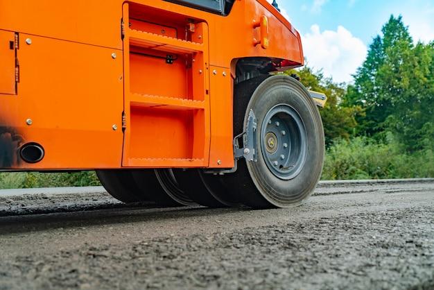 Pomarańczowy walec drogowy tworzy nawierzchnię.