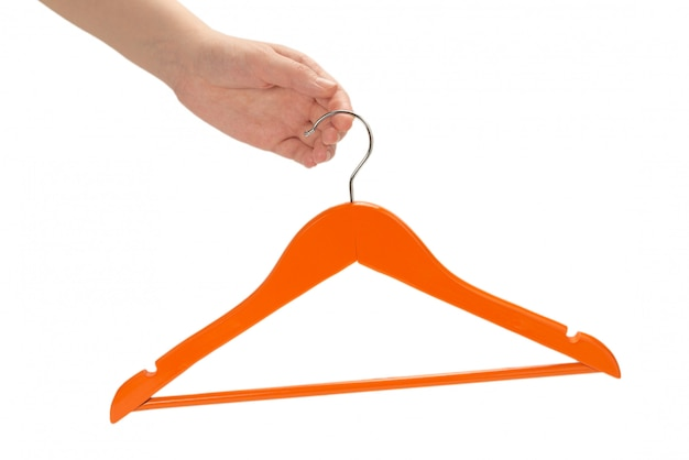 Pomarańczowy wieszak w ręce kobiety na białym tle.