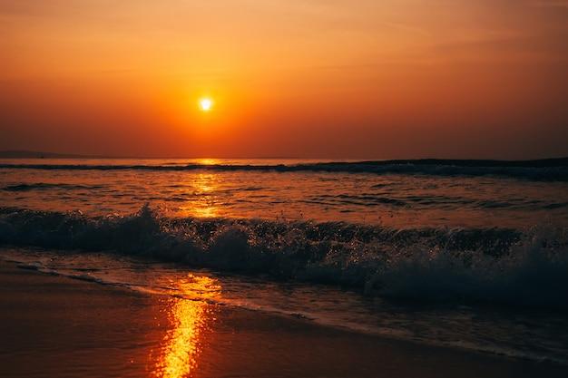 Pomarańczowy wschód słońca nad morzem z falami w lecie
