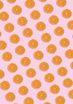 Pomarańczowy wzór na różowym tle. minimalna koncepcja świeckich płaskich.