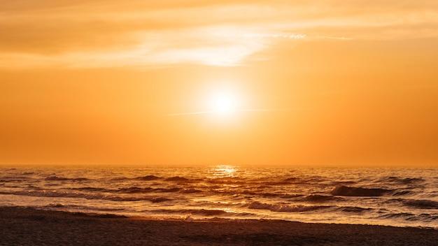 Pomarańczowy zachód słońca na plaży latem