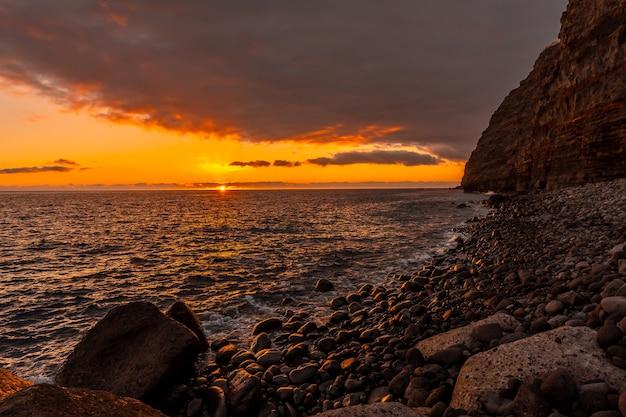 Pomarańczowy zachód słońca na plaży puerto de tazacorte na wyspie la palma, wyspy kanaryjskie. hiszpania