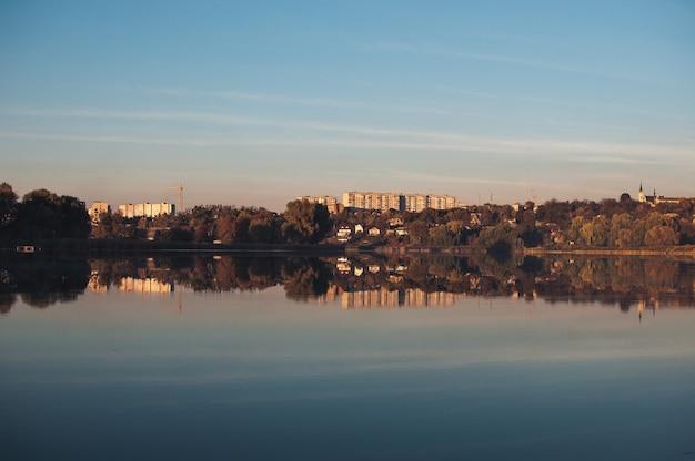 Pomarańczowy zachód słońca na tle rzeki we wrześniu w sezonie żniwnym. odbicie w wodzie z drzew.