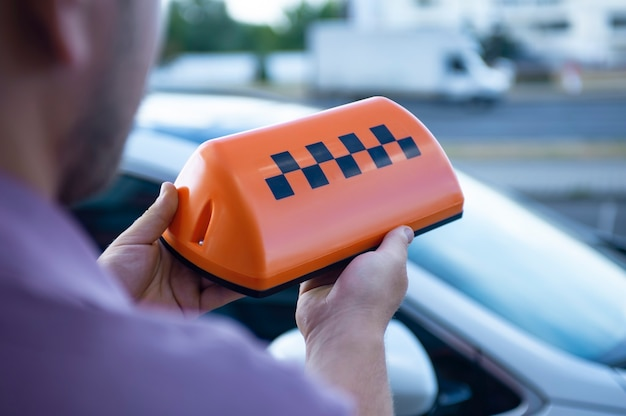 Pomarańczowy znak taksówki w rękach mężczyzny na tle samochodu.