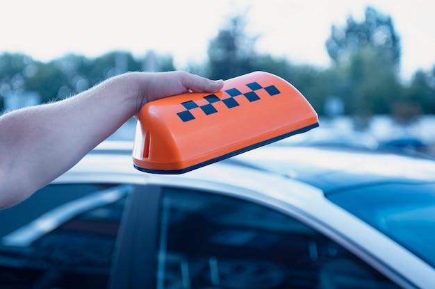 Pomarańczowy znak taksówki w rękach mężczyzny
